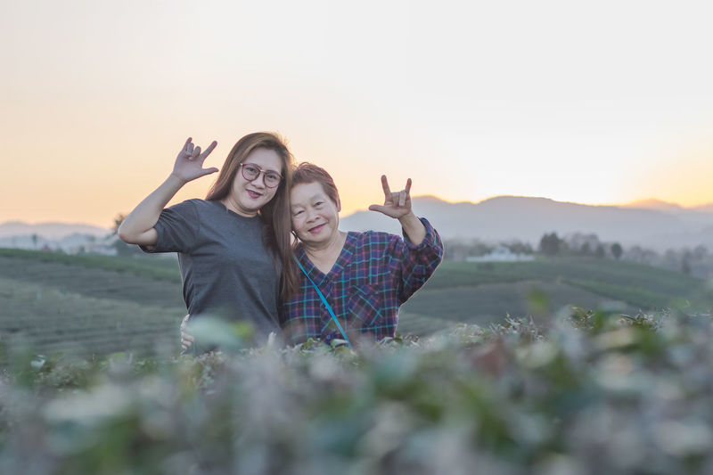 Portrait of mother and daughter gesturing on field against sky during sunset