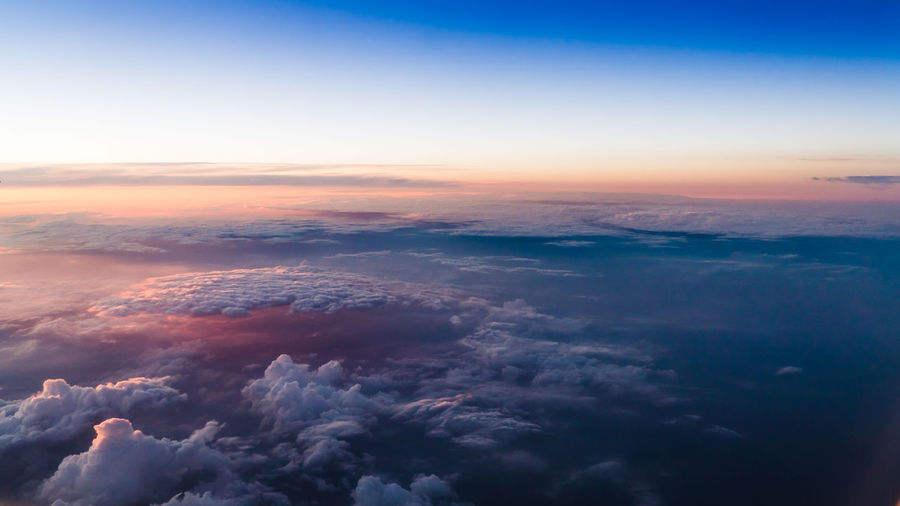 Birds-eye view down to clouds lit with a worm light of setting sun. Aerial View Backgrounds Beauty In Nature Blue City Cityscape Cloud - Sky Day Dusk Environment Horizon Landscape Natural Phenomenon Nature No People Outdoors Planet Earth Scenics Sky Space Sunset Tranquility