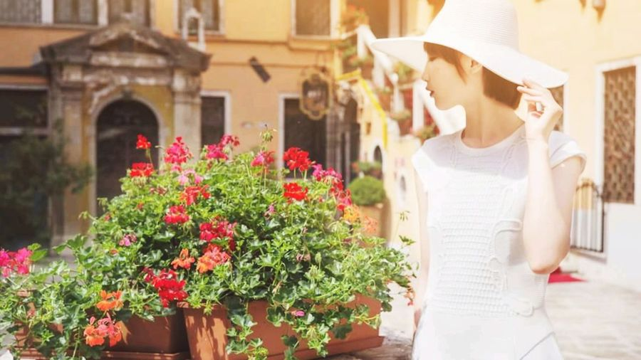 Woman wearing hat while standing by flowering plant