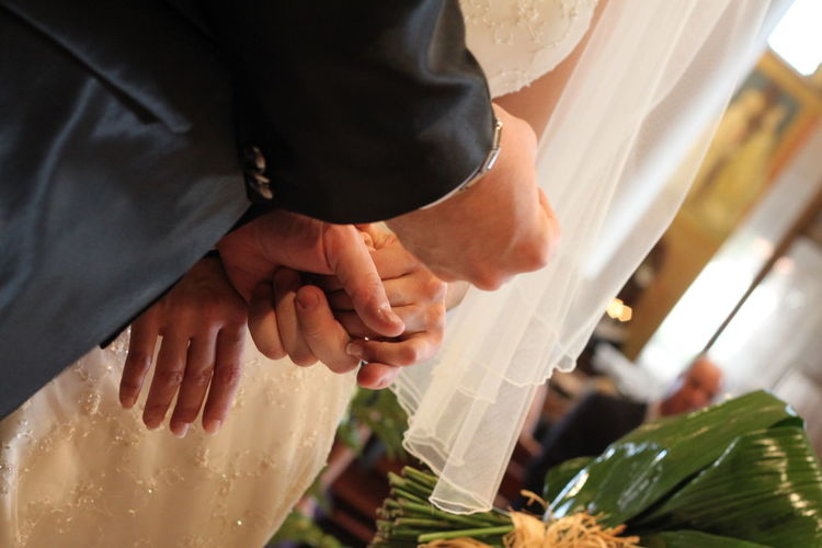 Midsection of newlywed couple standing during wedding