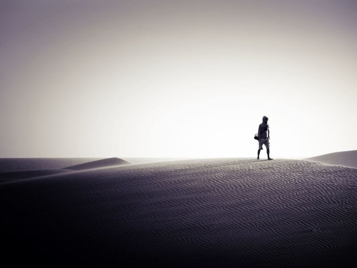 Alone man walking in desert