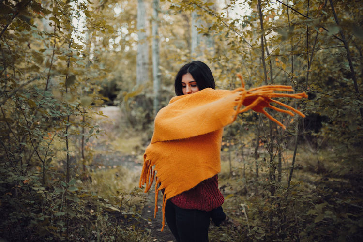 Woman wearing scarf standing against trees in forest