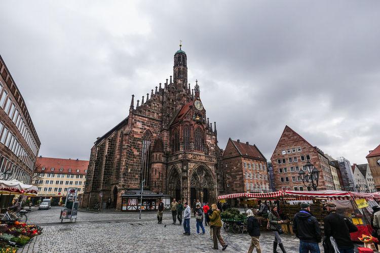 People walking on street by frauenkirche against cloudy sky