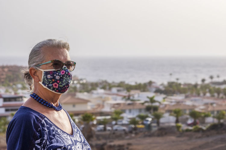 Close-up of senior woman wearing mask standing outdoors
