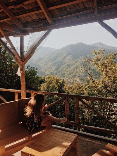 Woman sitting on railing by window