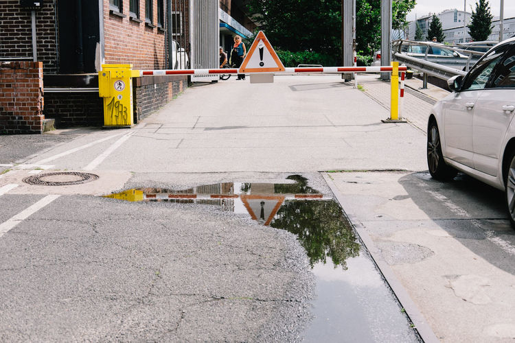 Caution Sign On Barrier Over Street With Reflection In Puddle