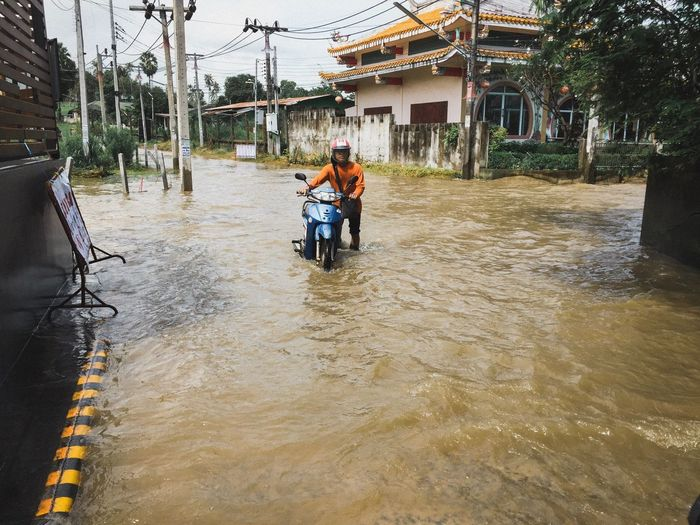 Men With Motor Scooter In Water On Road During Flood