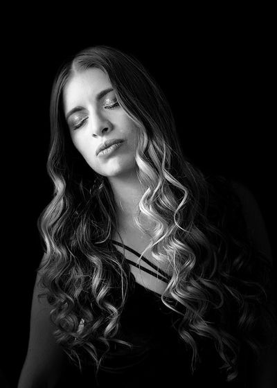 Beautiful young woman with eyes closed against black background
