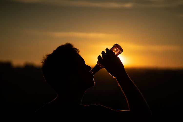Silhouette man drinking beer against orange sky