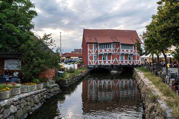 Bridge over canal amidst buildings against sky