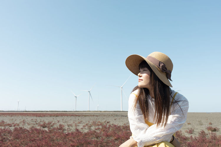 Woman wearing hat standing against clear sky