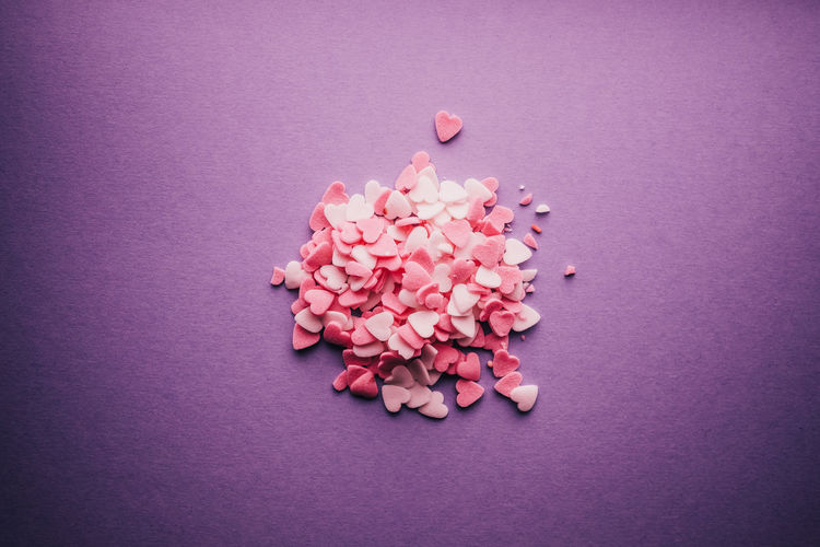 Close-up of pink heart shape candies on purple background