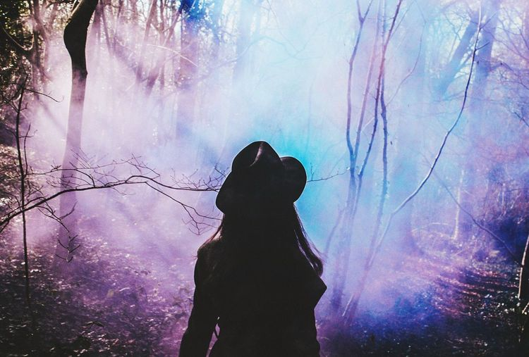 Rear view of woman in forest with colorful smoke