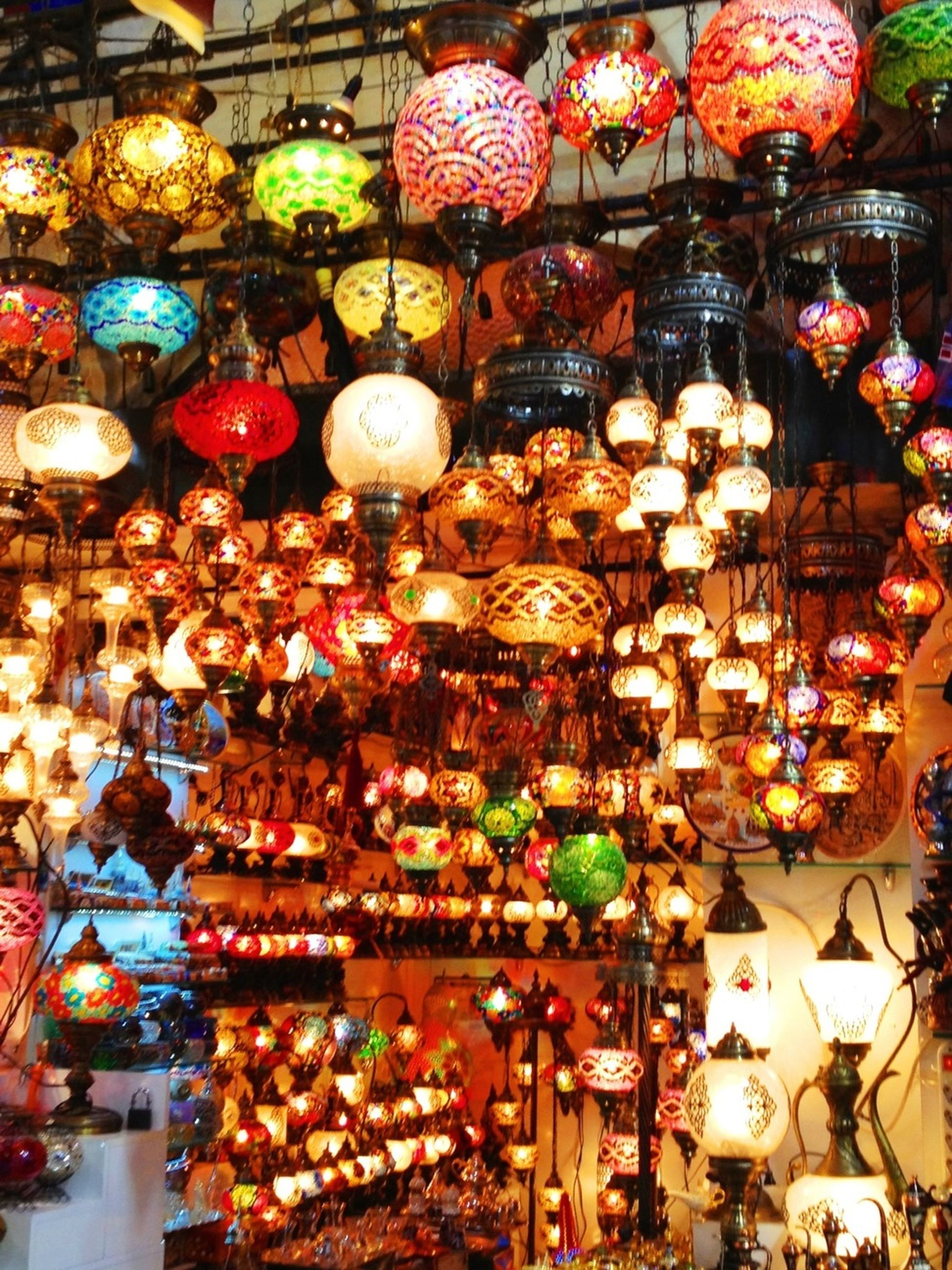 for sale, retail, abundance, large group of objects, variation, choice, indoors, arrangement, hanging, illuminated, market, decoration, market stall, lighting equipment, store, display, collection, in a row, lantern, multi colored