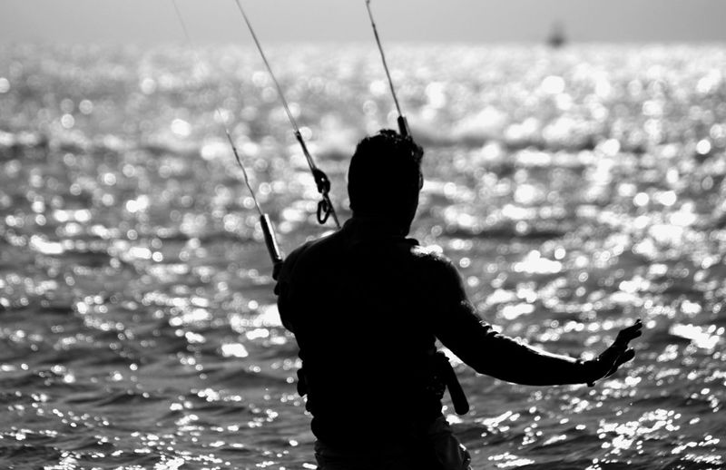 Rear view of silhouette man kiteboarding on sea