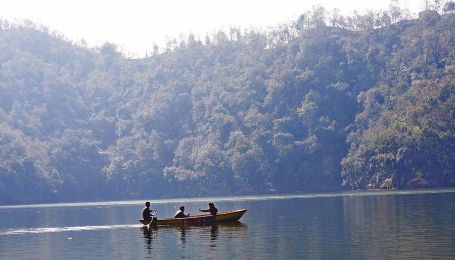 Boating In Calm Lake Against Lush Foliage