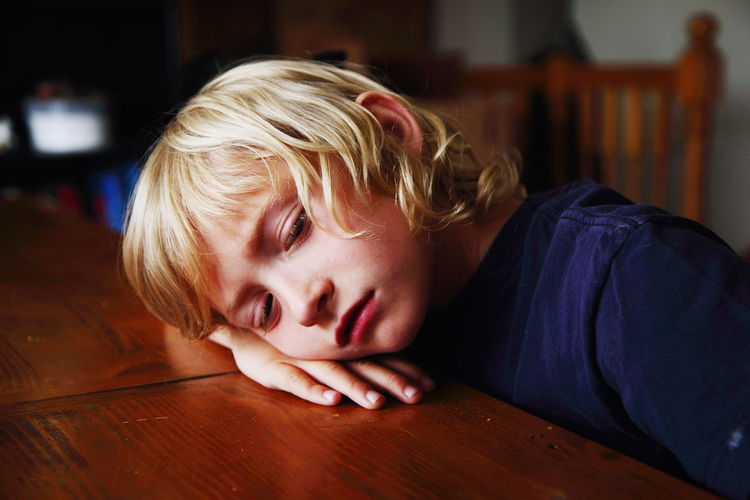Bored Blond Boy Resting Head On Table At Home