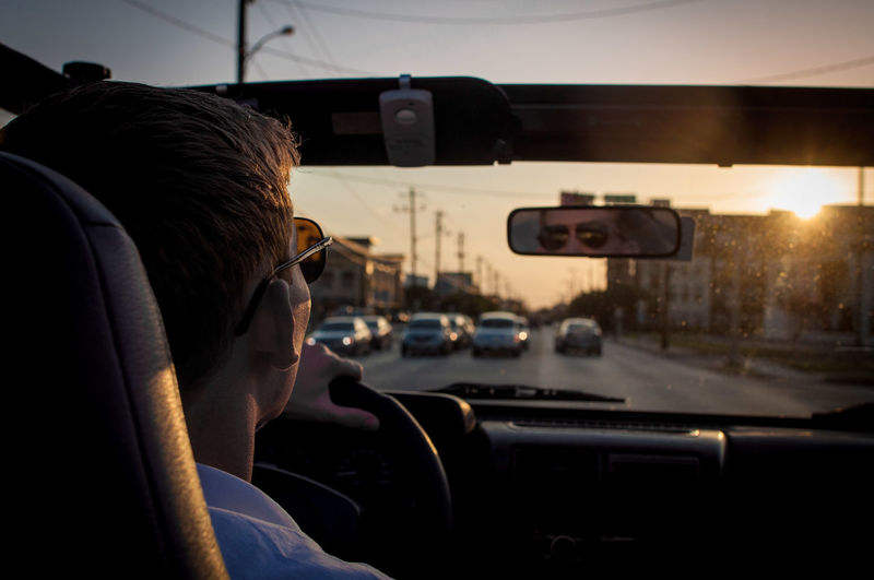 Young man driving car on street at dusk
