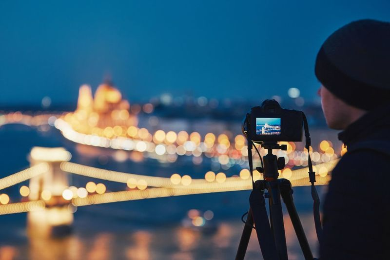 Man Photographing Illuminated Chain Bridge From Camera In City At Night