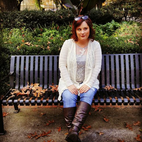 Smiling woman sitting on bench at park