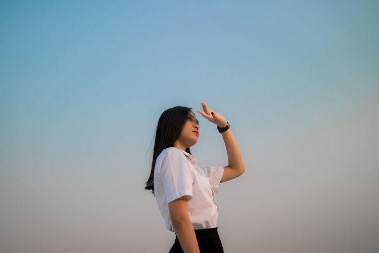 Low angle view of young woman shielding eyes standing against sky during sunset