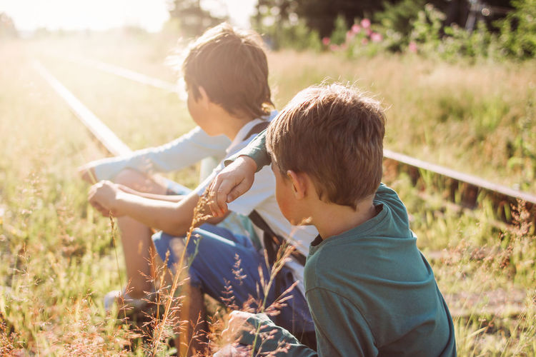 Boys sitting on railroad track during sunny day