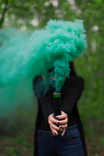 close-up of a girl holding green smokebomb against trees in forest Close-up Day Focus On Foreground Forest Front View Girl Green Color Holding Human Hand Leisure Activity Lifestyles One Person Outdoors People Real People Smoke - Physical Structure Standing Tree Young Woman