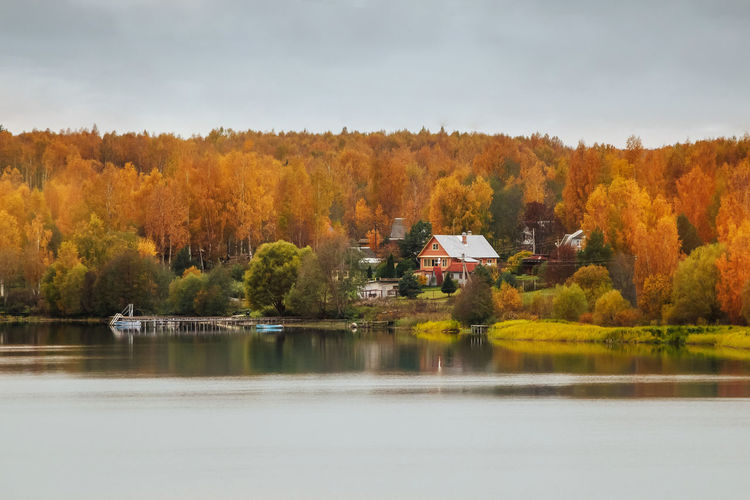Scenic view of lake by trees and houses against sky