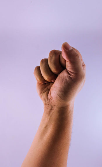 Close-up of hand gesturing fist against purple background