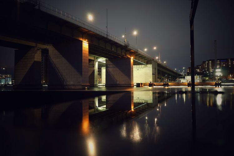 Bridge over illuminated city against sky at night