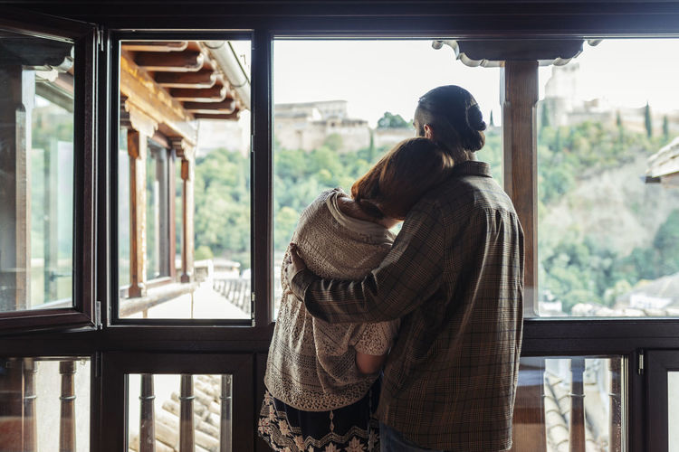 Rear view of couple standing against window