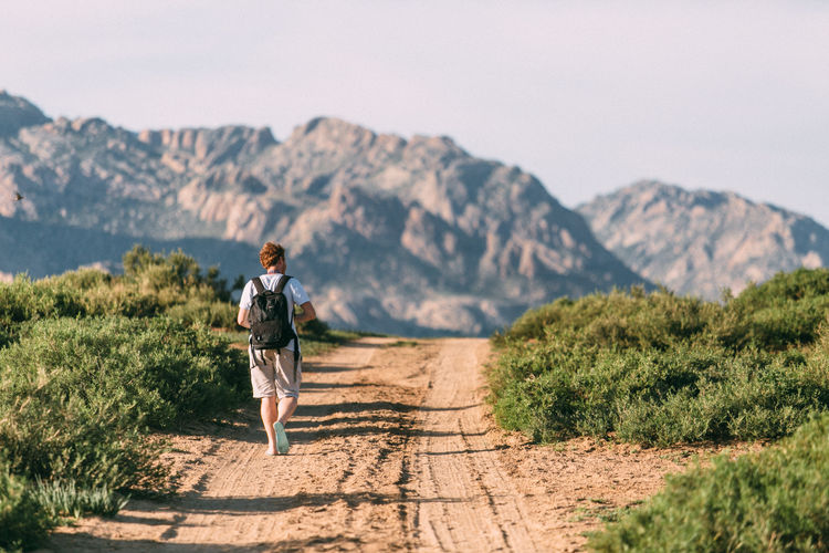 Rear view of man with backpack walking on dirt road against mountain