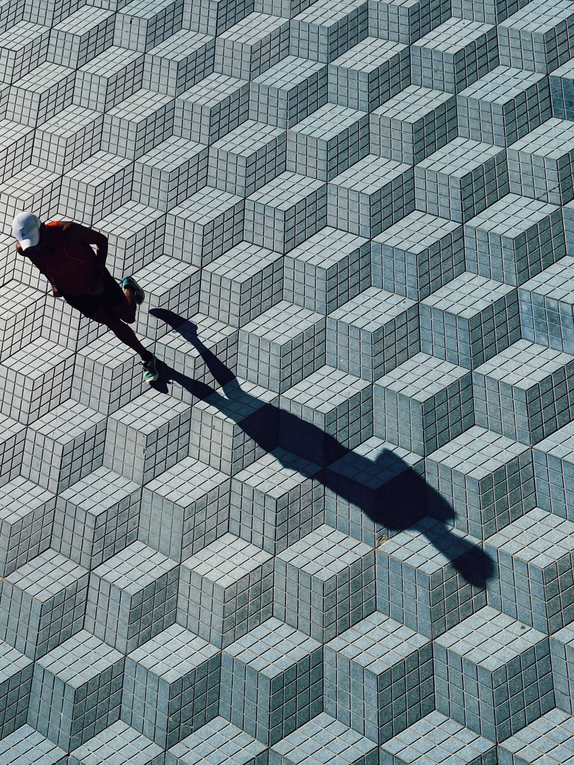 art, architecture, pattern, blue, line, built structure, city, wall, one person, flooring, building exterior, day, men, black, outdoors, high angle view, shadow