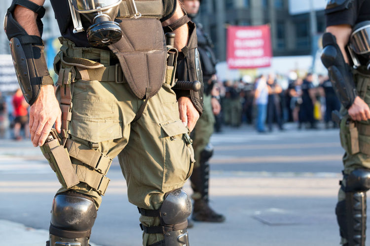 Midsection of army soldiers standing on street