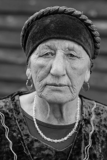 Russia close-up black-white portrait of a village elderly woman in a tatar dress