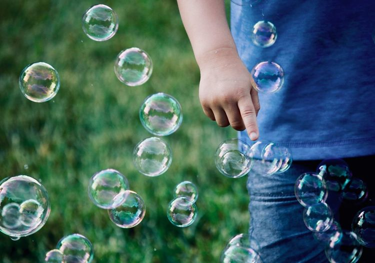 Popping bubbles in the backyard Outdoor Photography Popping Bubbles Boy Bubble One Person Human Body Part Fragility Vulnerability  Nature Day Leisure Activity Hand Body Part Human Hand Lifestyles Mid-air Bubble Wand Transparent Outdoors