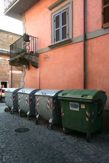 Dumpster of garbage under a building Pink Wall Balcony Building Building Exterior City Environmental Issues Garbage Garbage Bin Garbage Can House Houses And Windows Italy Lazio Outdoors Street Via Amerina Window