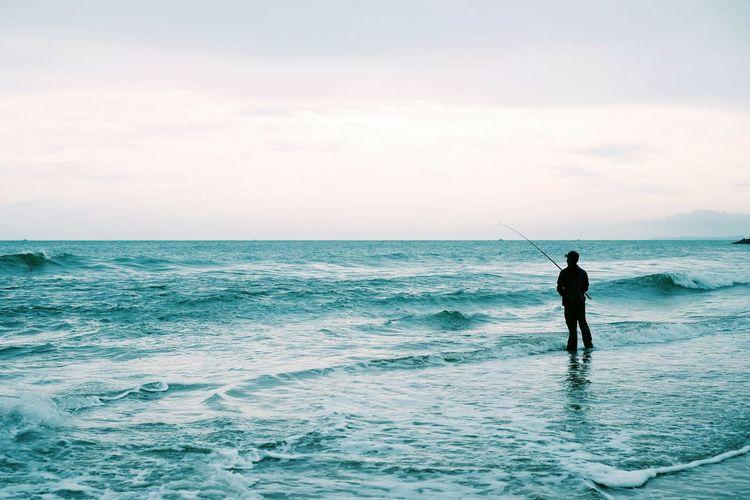 Rear view of man fishing at sea shore