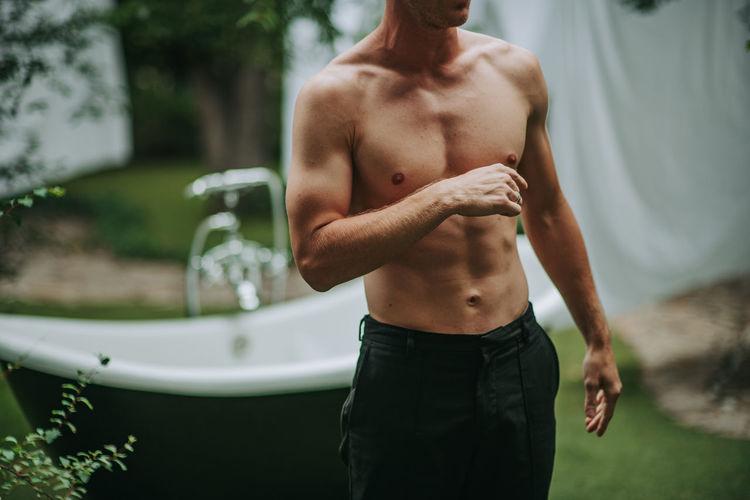 Full length of shirtless man standing outdoors