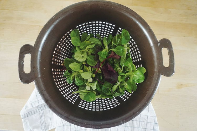 Directly above shot of fresh salad in colander on table