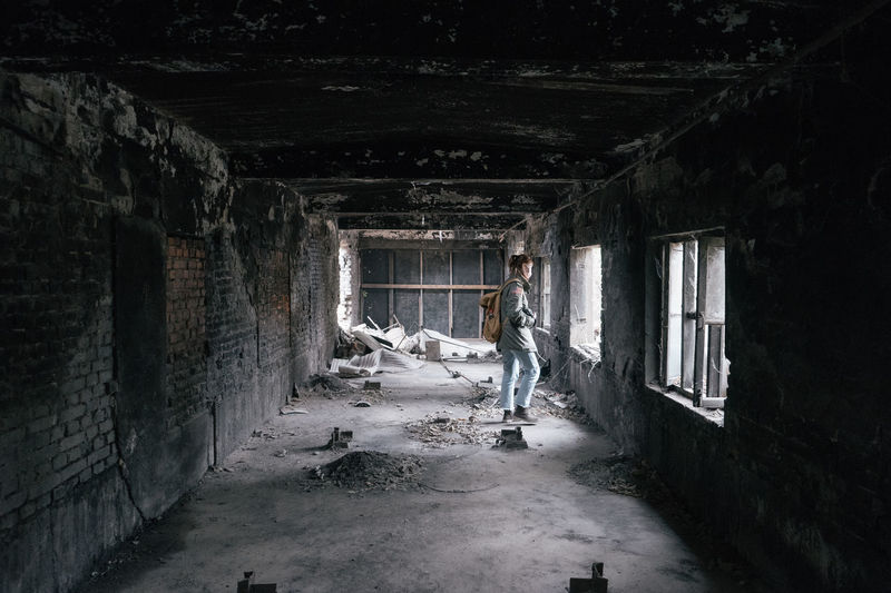 Side view of young man standing in abandoned building