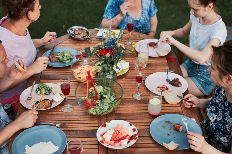 Family having a meal from grill during summer picnic outdoor dinner in a home garden