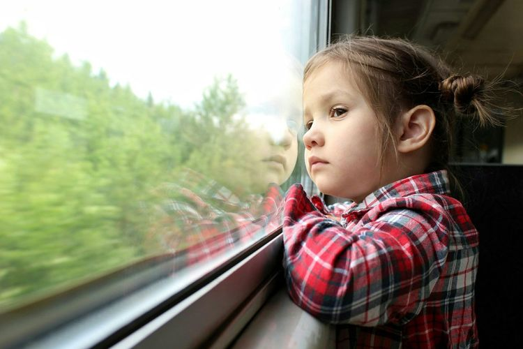 Cute Girl Looking Through Window Of Train