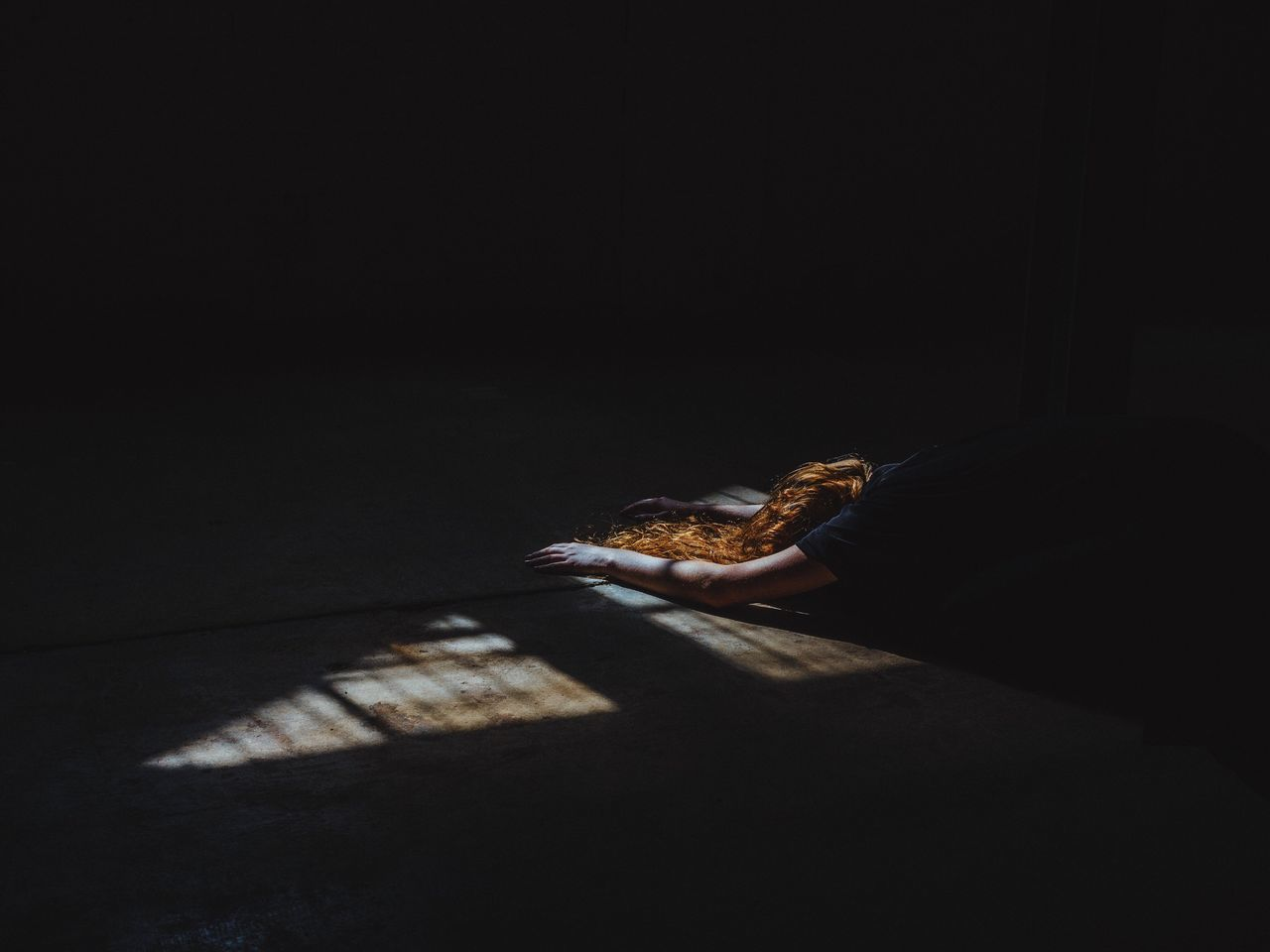 Sunlight falling on woman bending in darkroom