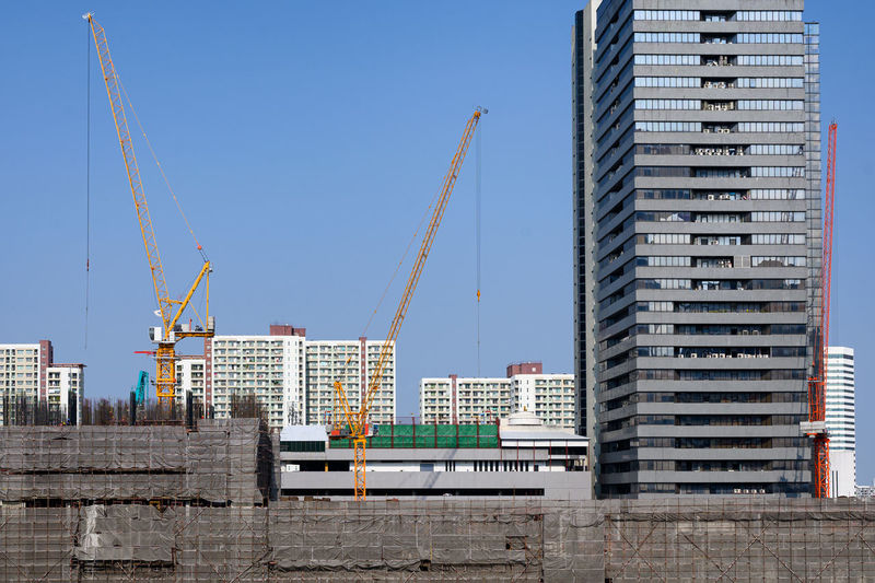 Construction site by buildings against clear sky