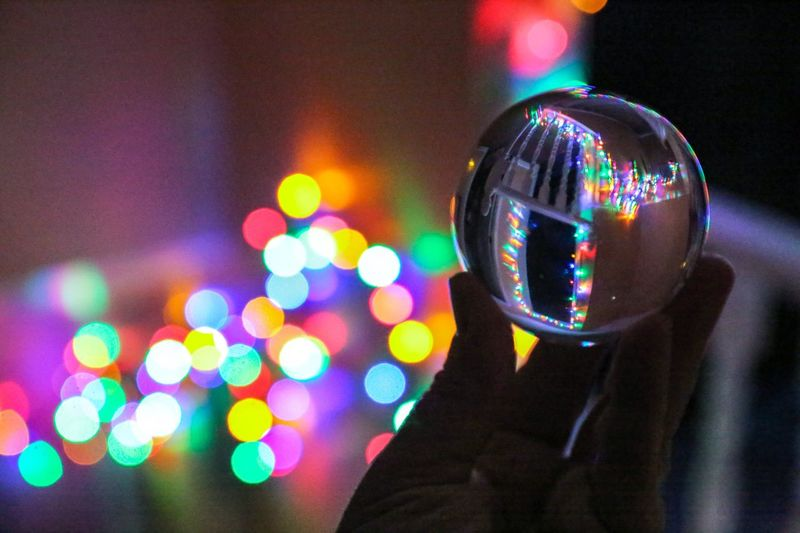 """""""Like snowflakes, my Christmas memories gather and dance—each beautiful, unique, and gone too soon."""" Deborah Whipp Glass Christmastime Multi Colored Illuminated Sphere Reflection Night Bubble Holiday Moments Defocused Focus On Foreground Shiny Close-up Nightlife Decoration Selective Focus"""