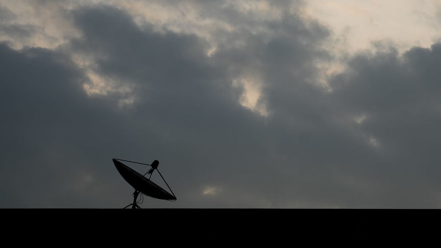 Silhouette of satellite located on the top of building deck with cloudy sky background, selective focus. Building Deck Weather Cloud - Sky Communication Llittleleaves Low Angle View Outdoors Sattlelite Scenics Silhouette Storm Cloud Telecommunication Tranquility Zoom