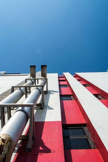 Tilt image of building against clear blue sky