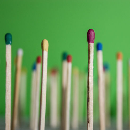 Close-up of colorful matchsticks on green background