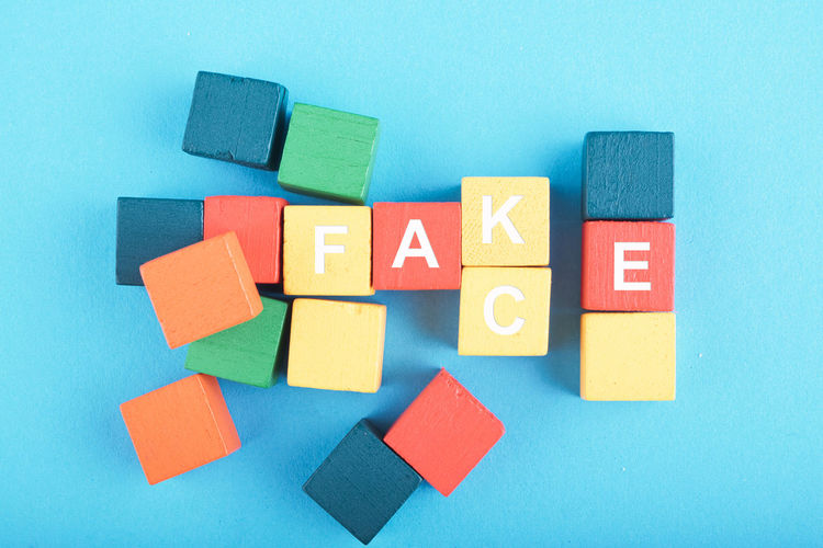 FACT OR FAKE word on colorful wooden cube over blue background Multi Colored Indoors  Blue No People Toy Still Life Toy Block Creativity High Angle View Shape Geometric Shape Close-up Variation Choice Red Large Group Of Objects Studio Shot Group Of Objects Colored Background Blue Background